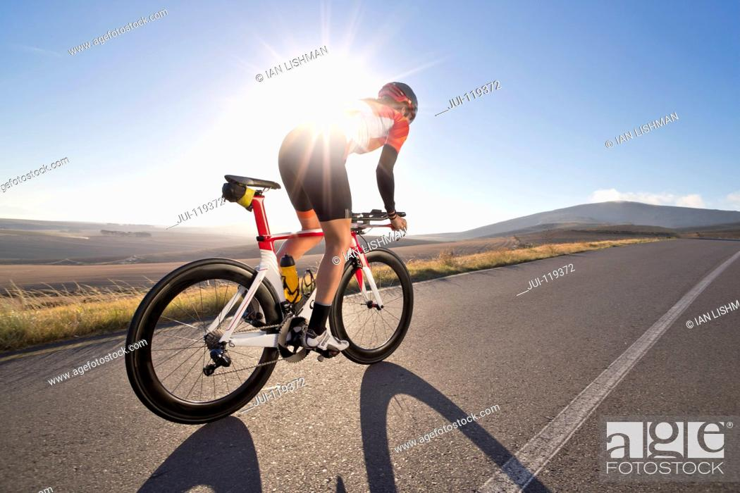 Stock Photo: Female cyclist riding race bicycle on sunny open road.