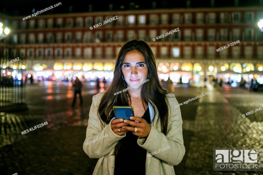 Stock Photo: Portrait of a woman using her smartphone on Plaza Mayor at night, Madrid, Spain.