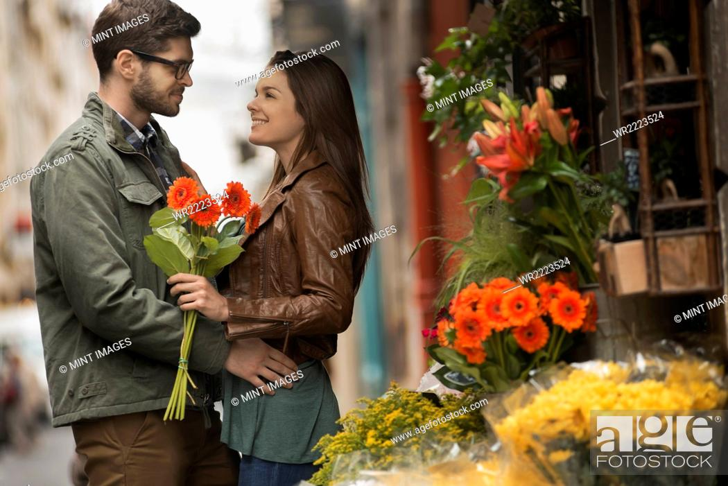 A man and woman by a flower stall in the city, holding a