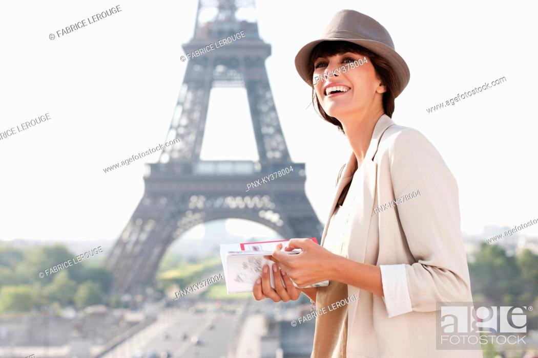 Stock Photo: Woman holding a guide book with the Eiffel Tower in the background, Paris, Ile-de-France, France.