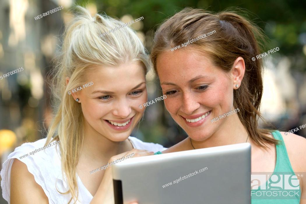 Stock Photo: Germany, North Rhine Westphalia, Cologne, Young women using digital tablet, smiling.