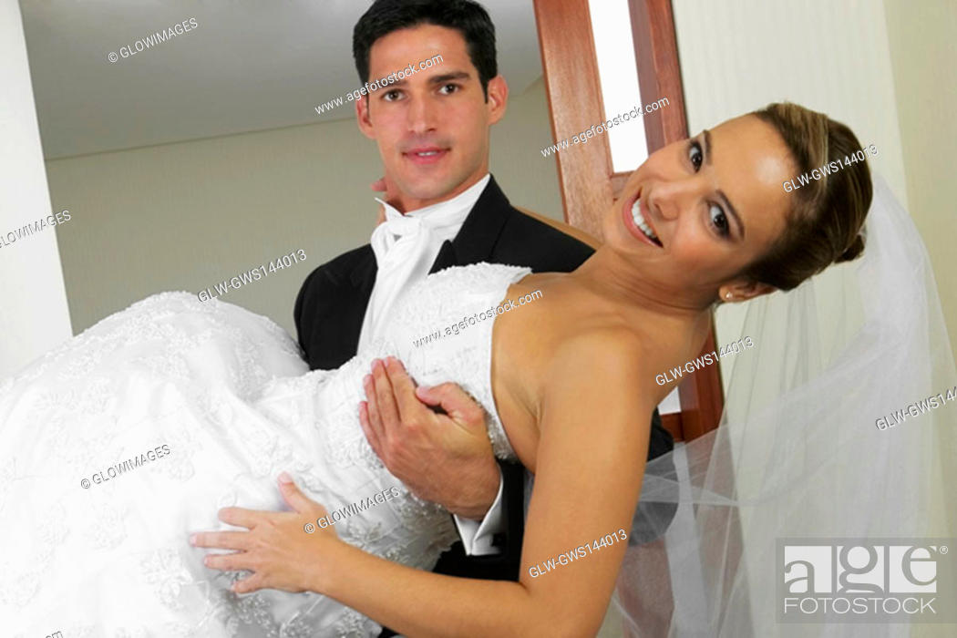 Stock Photo: Portrait of a groom carrying his bride.