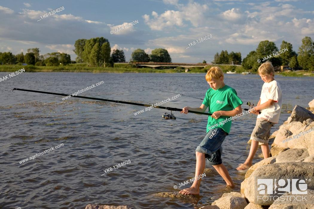 Stock Photo: Two Teenage Boys Fishing on Pier by Lake Võrtsjärv in Estonia.