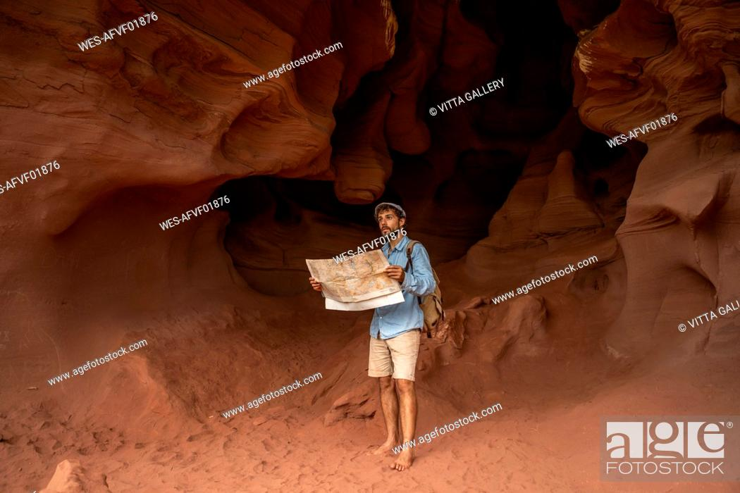 Imagen: Young man standing in a cave, looking at map.
