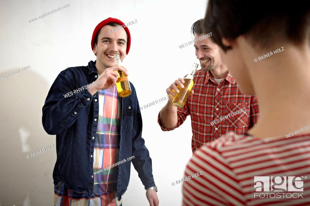 Stock Photo: Germany, Cologne, Men and woman drinking beer, smiling.