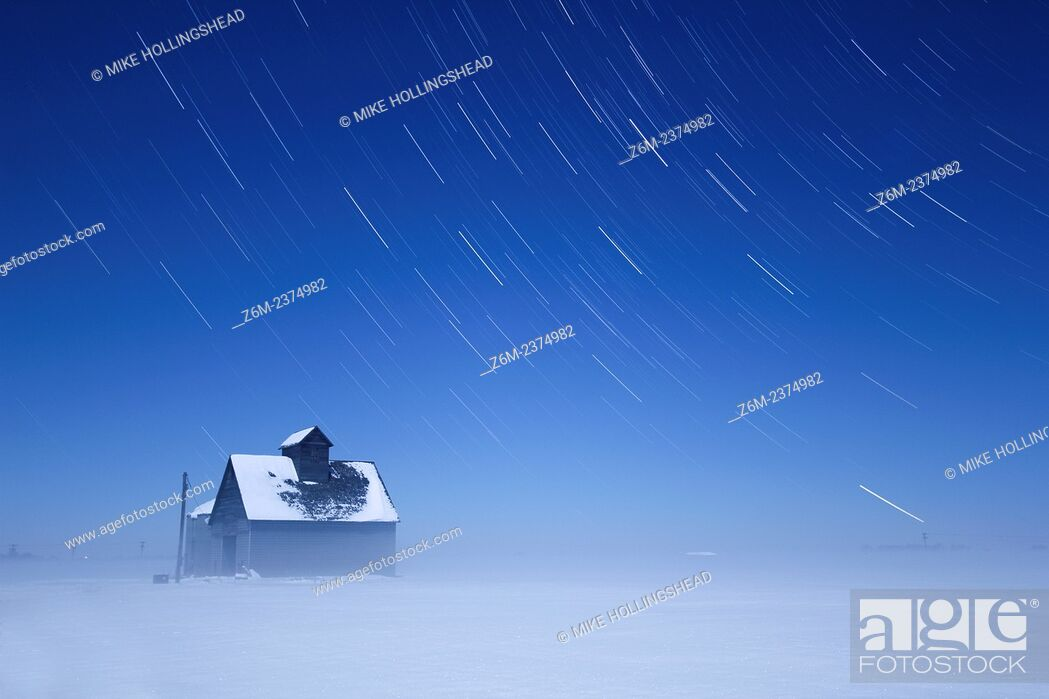 Stock Photo: Moon lights a foggy winter scene over western Iowa as stars trail above a barn.