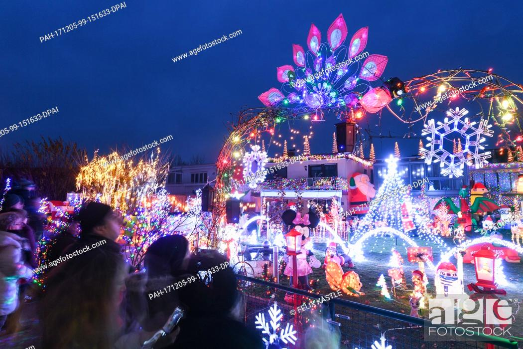 Stock Photo: Dozens of illuminated Christmas figures and motives, as well as thousands of lights fill the front garden of a house while music completes the experience for.