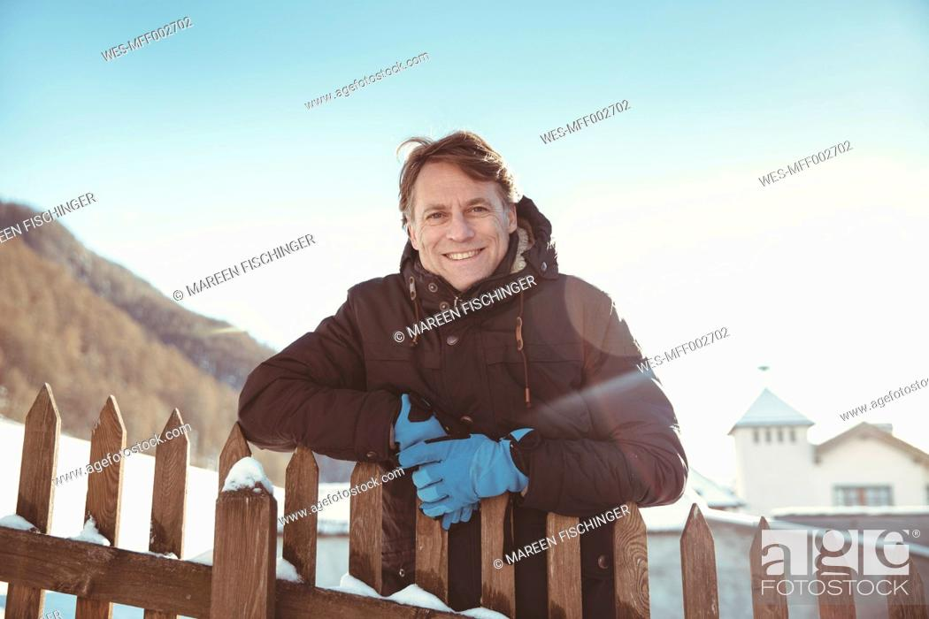 Stock Photo: Italy, Val Venosta, Slingia, portrait of smiling mature man standing at fence.