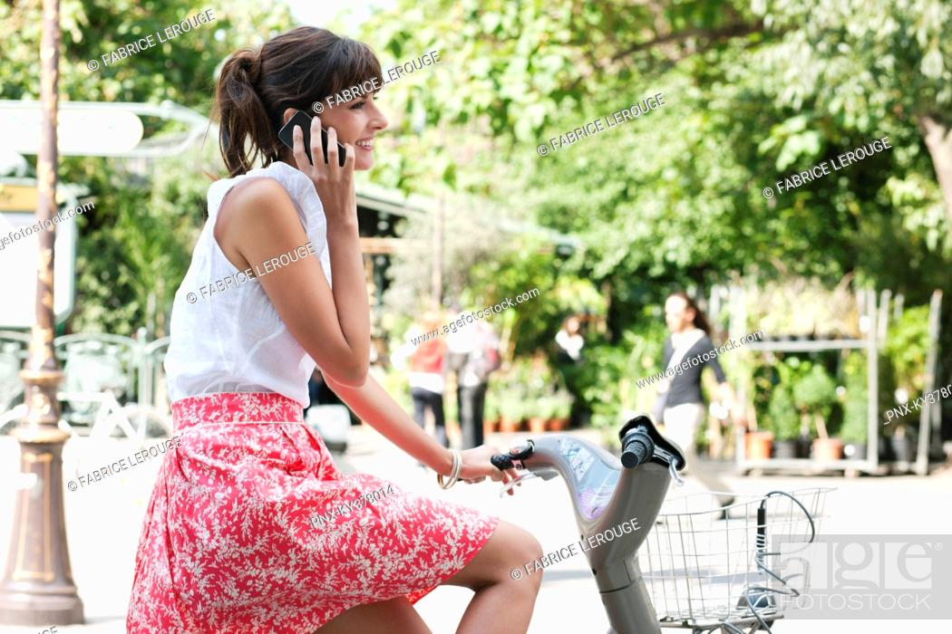 Stock Photo: Woman riding a bicycle and talking on a mobile phone, Paris, Ile-de-France, France.