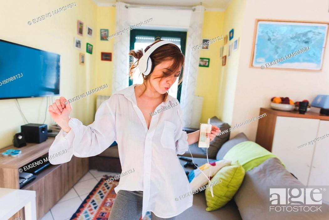 Imagen: Young woman in sitting room dancing to smartphone music on headphones.