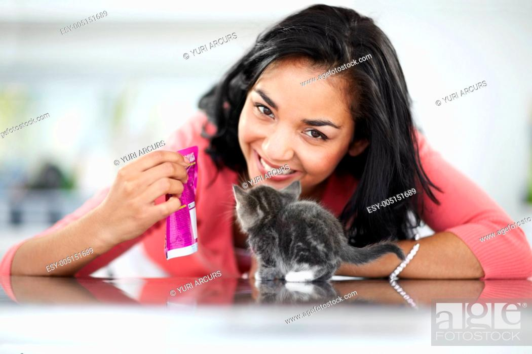 Stock Photo: Happy young woman showing her kitten a sachet of cat food.