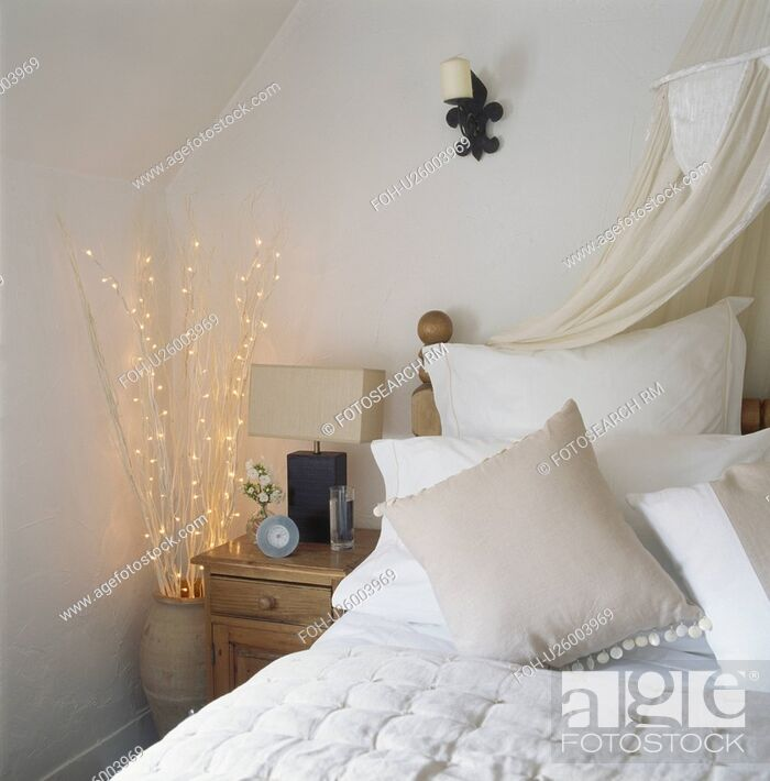 Stock Photo Beige Cushions And With White Pillows On Bed In Bedroom Pot Of Twigs Fairy Lights