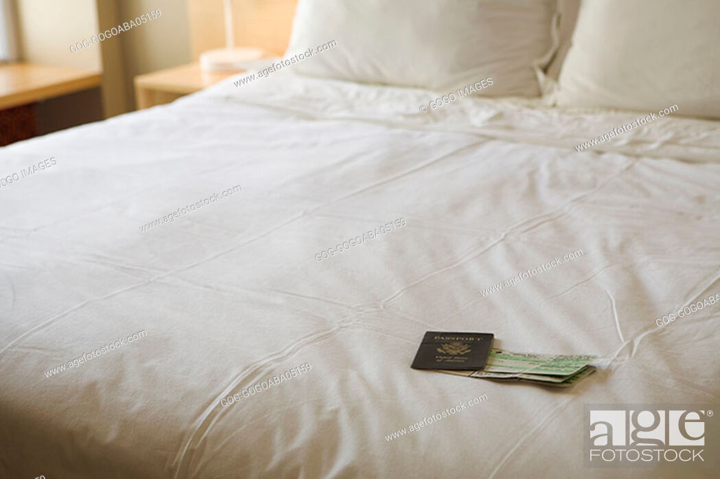Stock Photo: Passport and airplane tickets on made bed.