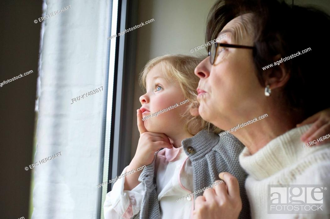 Stock Photo: Woman with her granddaughter looking through a window.