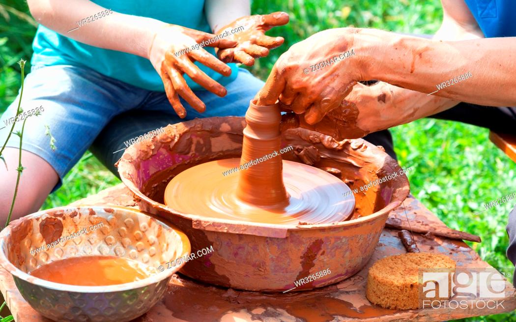 Stock Photo: Teacher helps his student to work with red clay. Work on the potter's wheel at the outdoors.