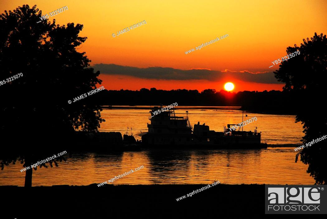 Imagen: A River Barges Glides past the Setting Sun Alng the Mississippi River near Memphis, TN.