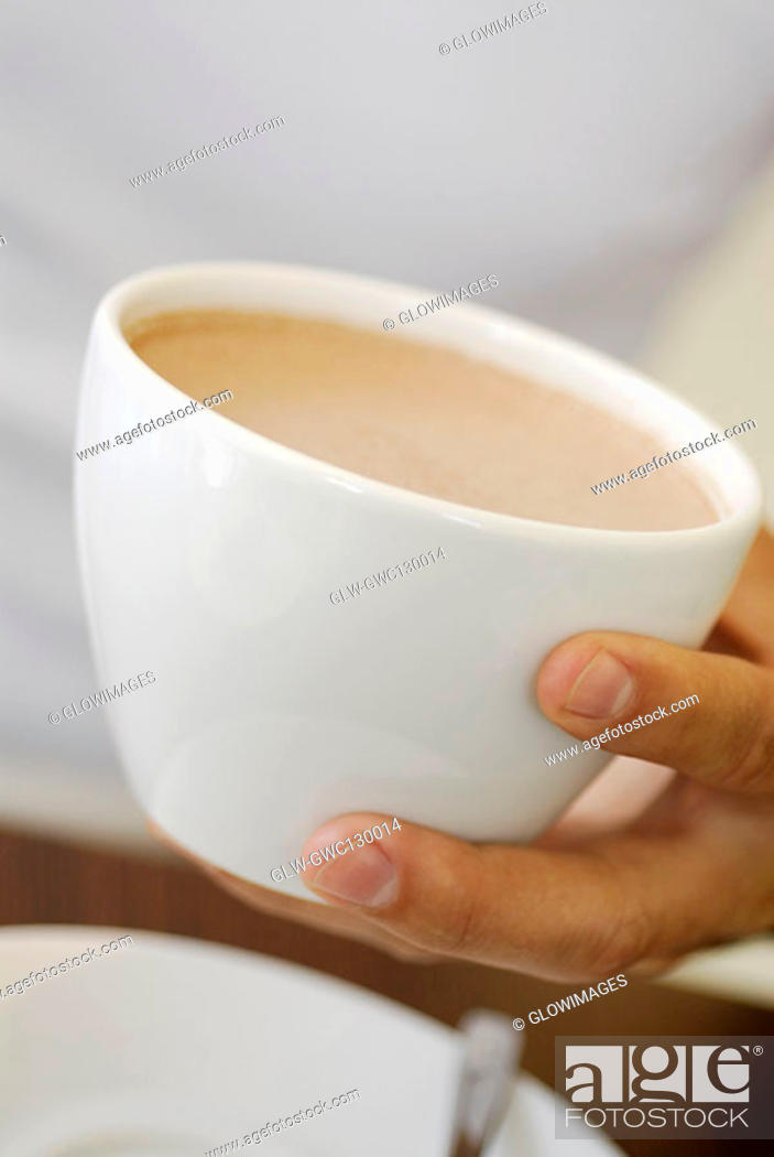 Stock Photo: Close-up of a person's hand holding a cup of coffee.