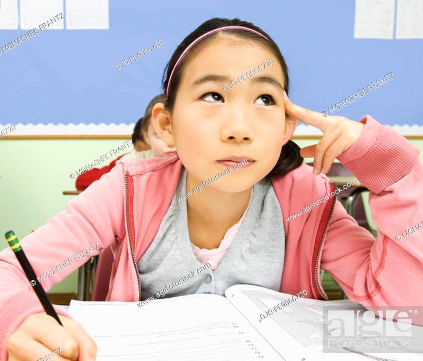 Stock Photo: Girl writing in workbook in classroom.