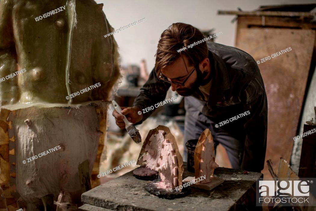 Imagen: Sculptor in artists' studio creating sculpture.