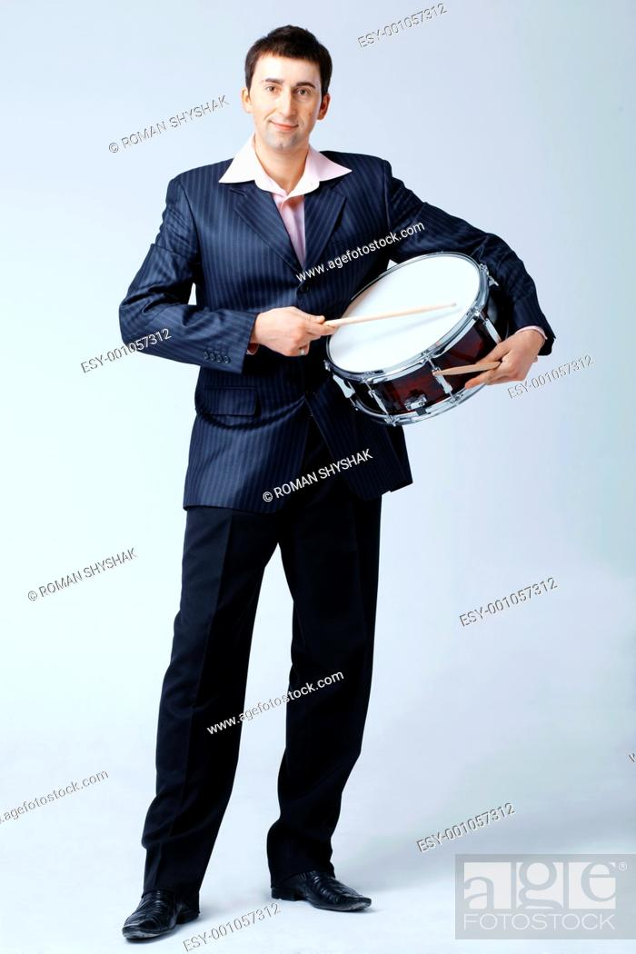 Stock Photo: Man in suite is playing on the drum with drumsticks, full length.