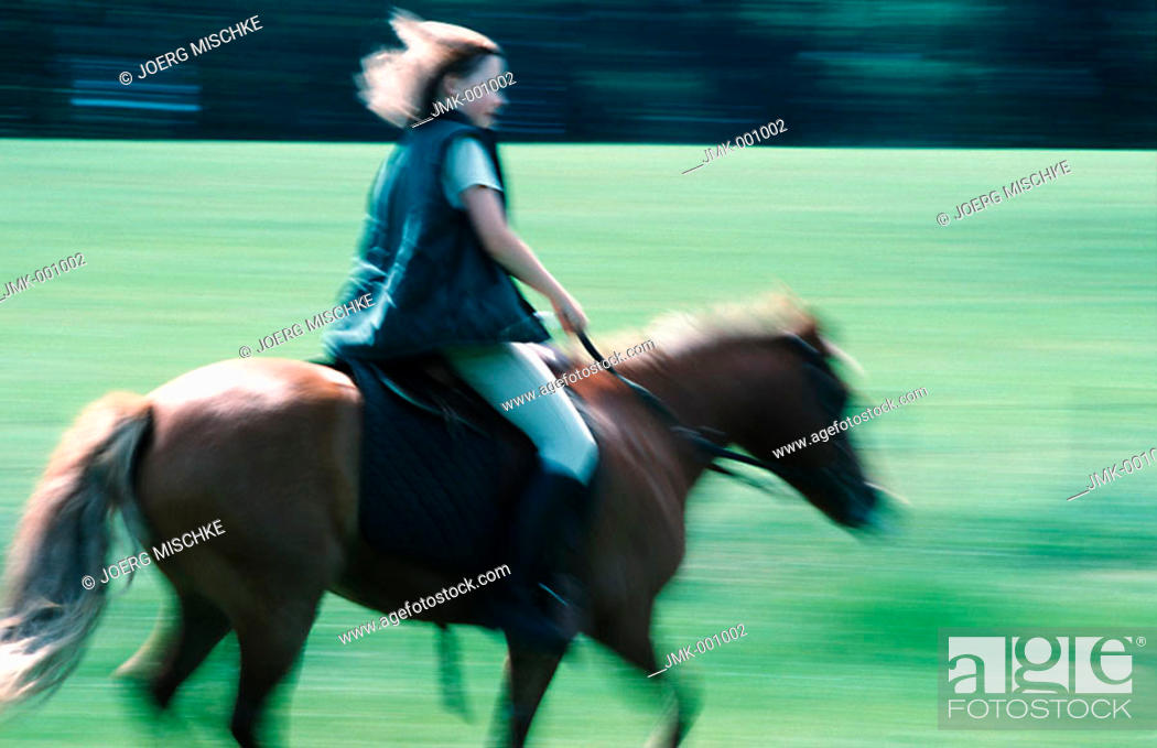 Stock Photo: A girl riding a horse in the open countryside.