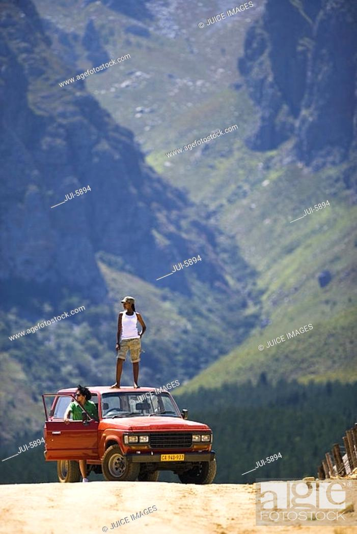 Stock Photo: Young couple, in mid-distance, standing beside parked jeep on dirt track in mountain valley, woman on roof.