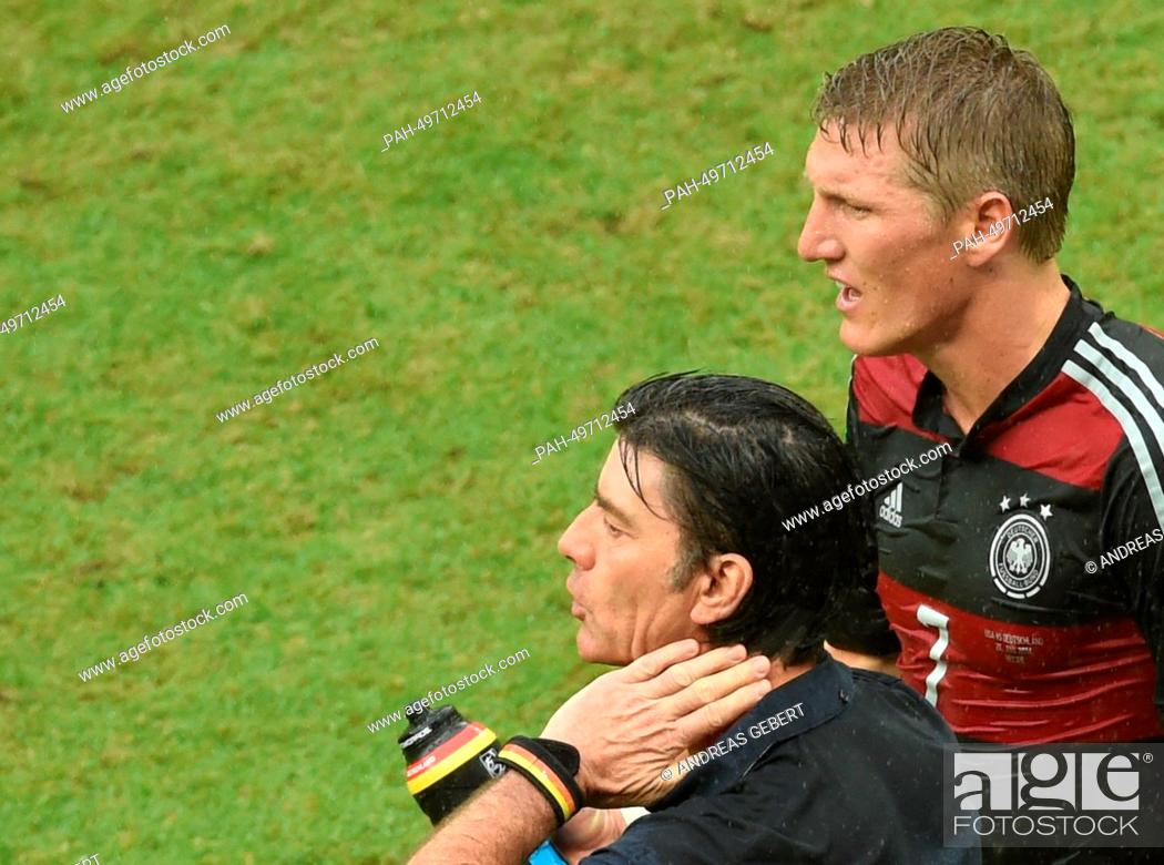 Germany's Bastian Schweinsteiger stand next to German head coach ...