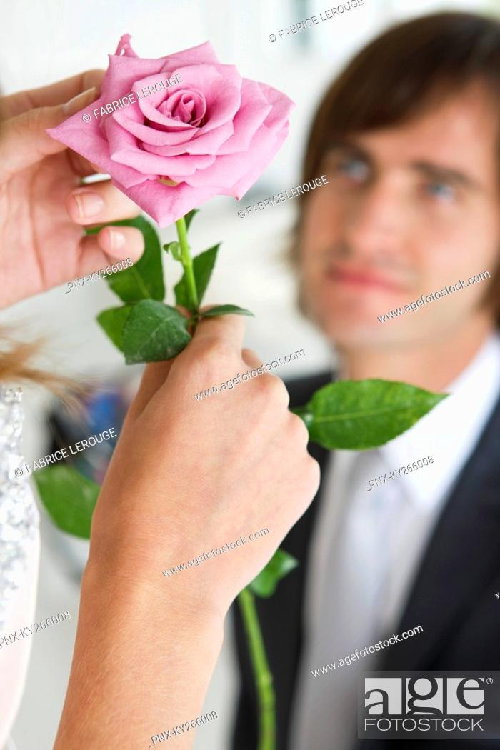 Stock Photo: Woman holding a flower in front of a man.