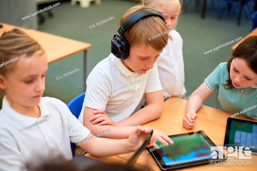 Stock Photo: Schoolboys and girls looking at digital tablets in class at primary school.