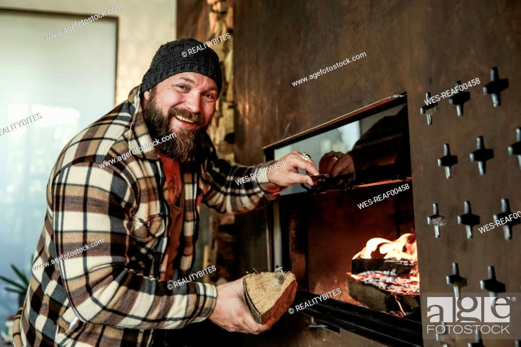Stock Photo: Portrait of bearded man in front of fireplace at home.