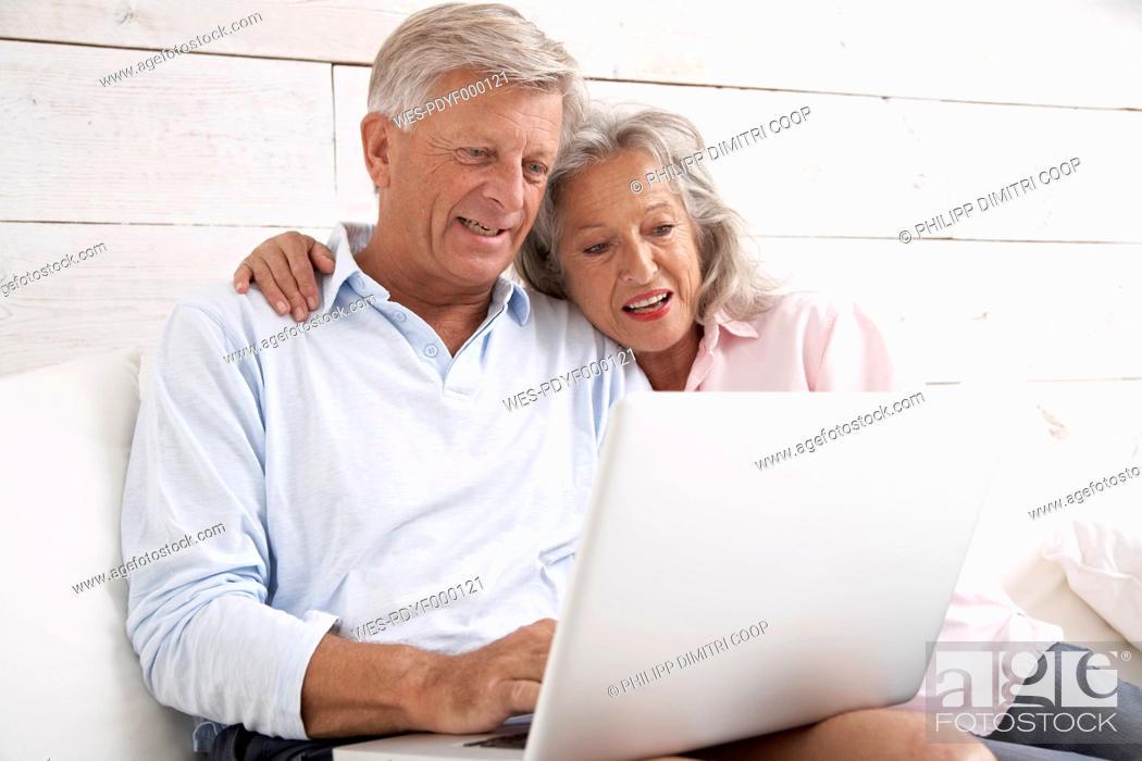 Stock Photo: Spain, Senior couple checking emails on laptop, smiling.