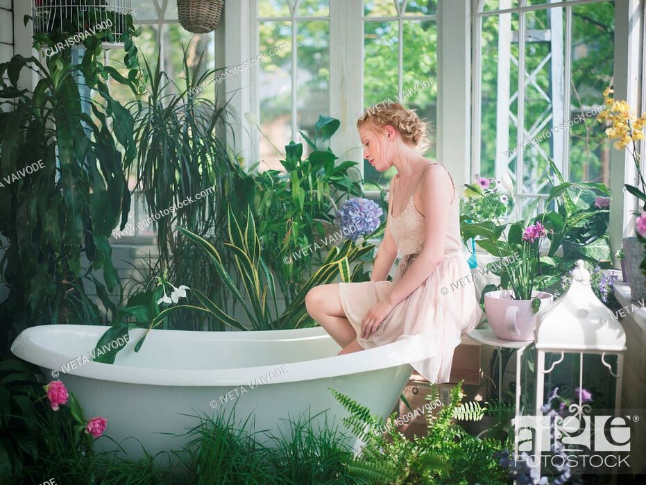 Imagen: Young woman, sitting on edge of bathtub, in bathroom filled with plants.