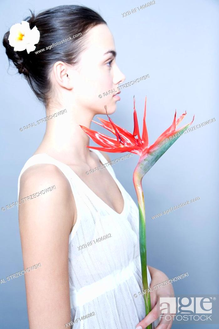 Stock Photo: young woman with bird of paradise flower.