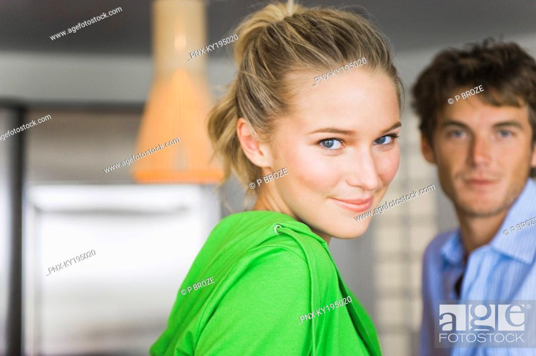 Stock Photo: Portrait of a woman smiling with a man in the background.