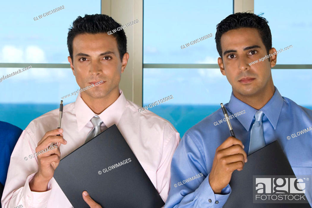 Stock Photo: Portrait of two businessmen holding pens.
