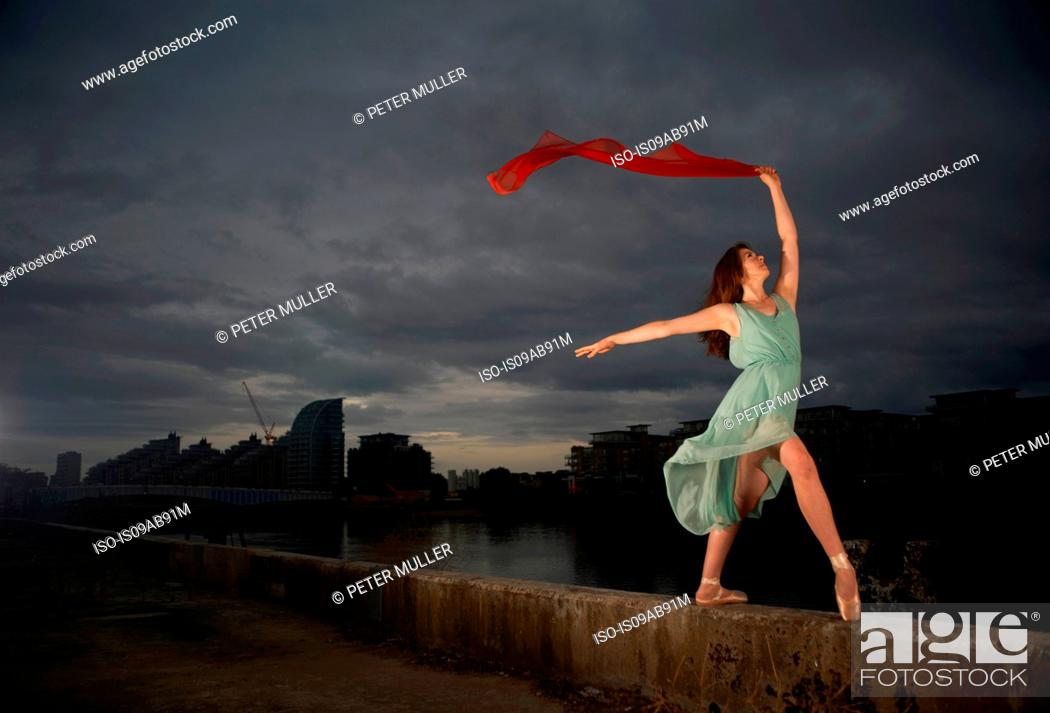 Stock Photo: Ballet dancer holding red scarf on wall.