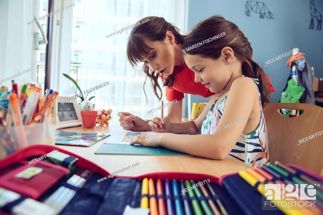 Stock Photo: Mother helping girl doing her schoolwork at home.