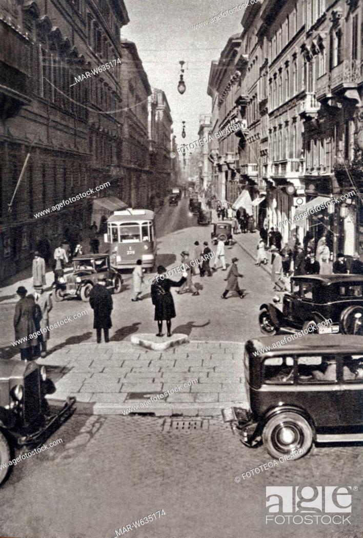 Stock Photo: ROMA Affollata scena di strada in Via del Corso a Roma: un vigile dirige il traffico tra automobili, pedoni e tramvai, 1933 circa, Copyright © Fototeca Gilardi.