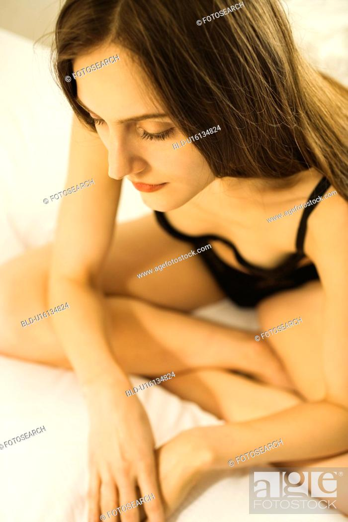 Stock Photo: Caucasian mid-adult woman sitting on bed in lingerie with legs crossed.