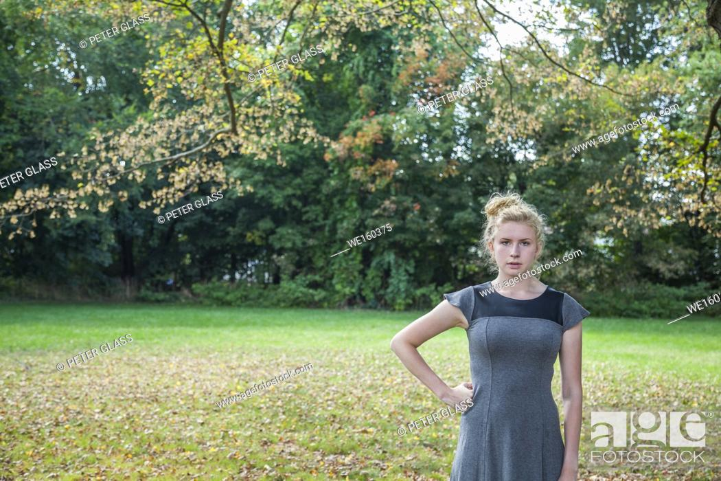 Stock Photo: Blonde teenage girl standing outdoors.