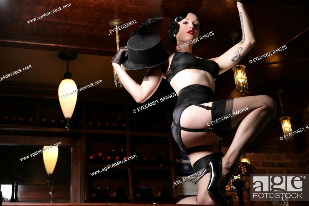 Stock Photo: Young sexy woman doing striptease in burlesque bar.