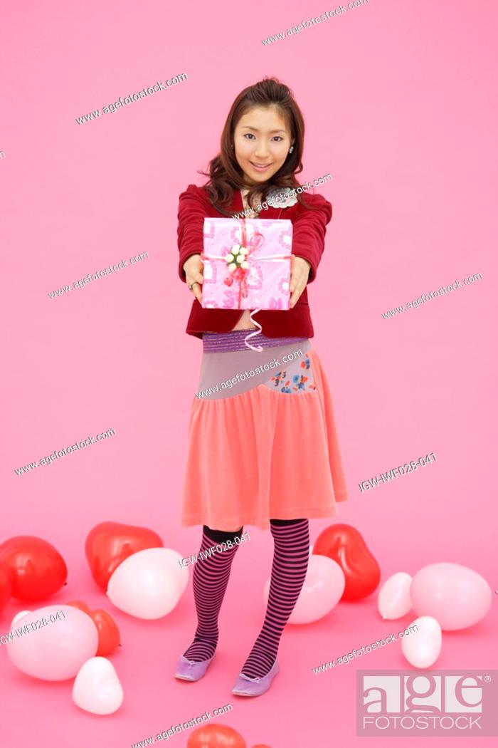 Stock Photo: Portrait of a teenage girl holding a gift box.