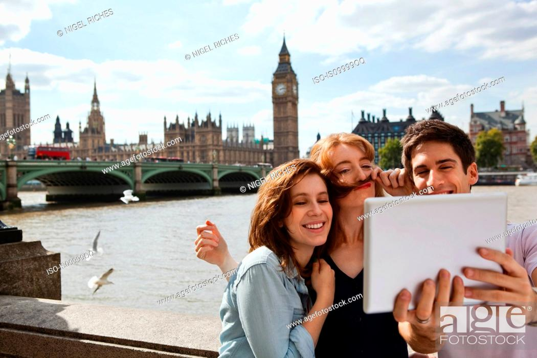 Stock Photo: Friends using a digital tablet in central London.
