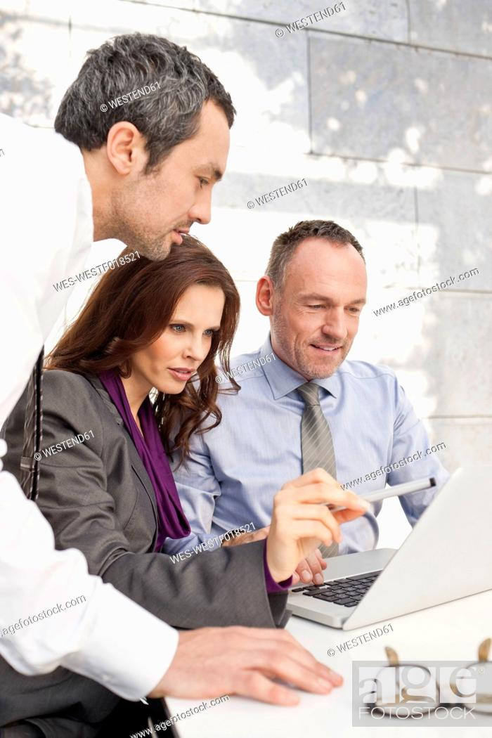 Stock Photo: Germany, Leipzig, Business people using laptop and discussing about wind power model.