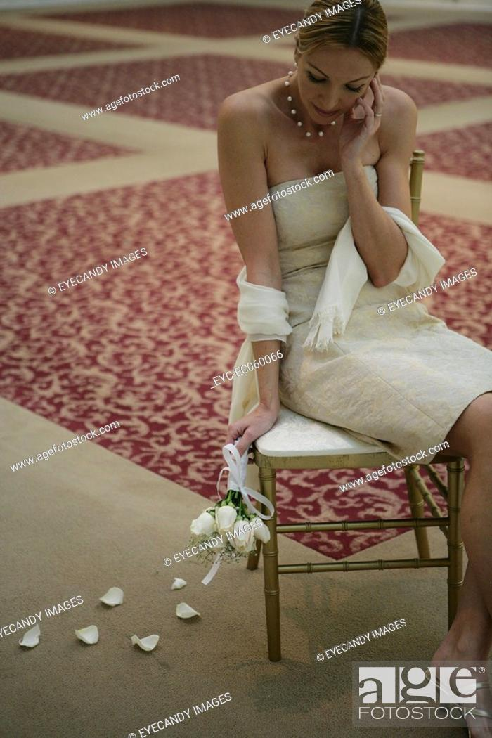 Stock Photo: Mature women sitting on a chair looking down.