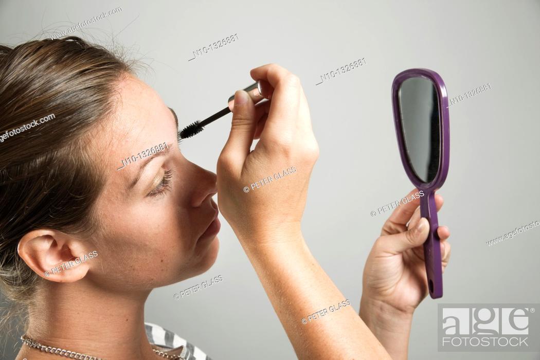 Stock Photo: Young woman applying makeup.