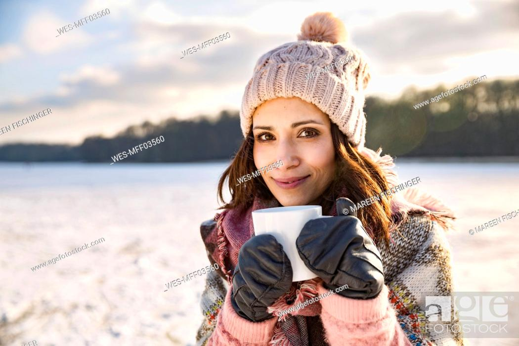 Stock Photo: Portrait of smiling woman drinking hot beverage from a cup outdoors in winter.