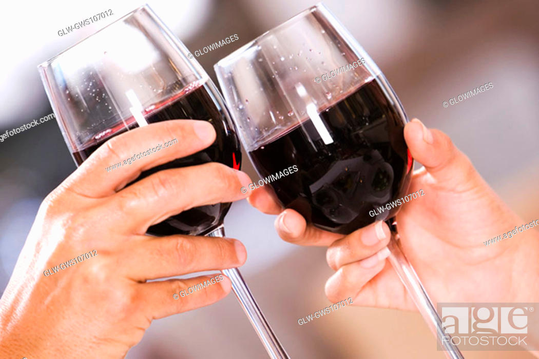 Stock Photo: Close-up of a man and a woman toasting glasses of red wine.