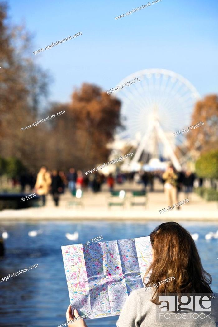 Stock Photo: Woman looking at map with Place de la Concorde, big wheel in background, Paris.