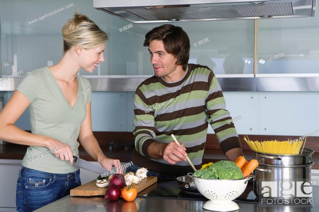Stock Photo: Young couple in modern kitchen, cooking together, smiling, looking at each other.